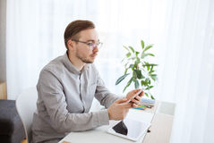 Creative male office worker texting on smarphone. Business, startup and people concept - businessman or creative male worker texting on smarphone at home office Stock Photos