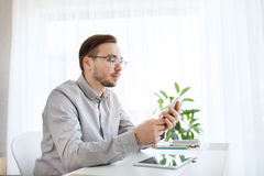 Creative male office worker texting on smarphone Stock Photos