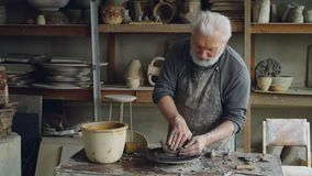 Creative male potter is forming unsymmetrical broad bowl on throwing wheel while working in small workshop. Creativity. Creative male potter is forming beautiful stock video footage