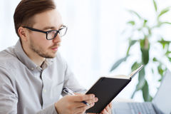 Creative male worker with book at home office Royalty Free Stock Images