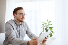 Creative male worker with tablet pc at home office Royalty Free Stock Images