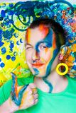 Man art make up. Creative man boy model orange blue yellow green colors. Bright conceptual art make-up glows light party time. Multicolored pins, clamps, clips Royalty Free Stock Photos
