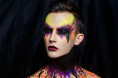 Man art make up. Creative man boy model purple pink yellow green colors. Bright conceptual art make-up glows light party time. Multicolored pins, clamps, clips Royalty Free Stock Photo