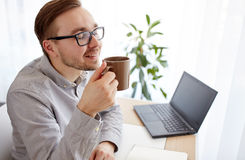 Creative man or businessman drinking coffee. Business, drinks and people concept - happy businessman or creative man drinking coffee at home office Stock Image