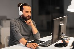 Creative man in headphones working at night office Stock Image