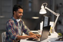 Creative man with laptop working at night office stock photo