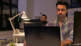 Creative man with laptop working at night office stock footage