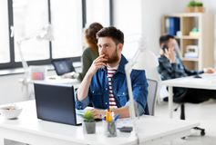 Creative man with laptop working at office Royalty Free Stock Image