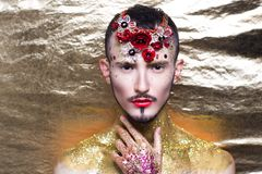 Man art make up. Creative man model red yellow golden colors. Bright conceptual art make-up glows light party time. Multicolored glitters, sequins, flower royalty free stock photos