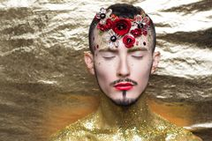 Man art make up. Creative man model red yellow golden colors. Bright conceptual art make-up glows light party time. Multicolored glitters, sequins, flower stock images