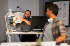 Creative man showing papers to colleague at office Royalty Free Stock Images
