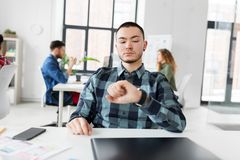 Creative man with smartwatch working at office Stock Image