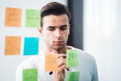 Creative man writing sticky note on glass wall at office space. Manager brainstorming new startup business stock photos