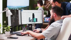 In creative media house two professional architects are using 3D software. To design new buildings. In the background - cozy and modern styled office stock video footage