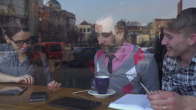 Creative meeting in the cafe of three young people stock footage