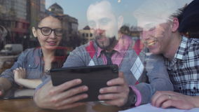 Creative meeting in a cafe of two young men and a girl. Young people are considering something on a tablet. They happily smiling. Teamwork, cooperation and stock footage