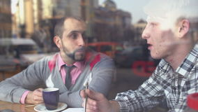 The creative meeting of two young men in a cafe. A man sitting at a table in front of a window. Men are sitting in front of the table and near window. Men stock video