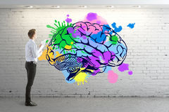Creative mind concept. Businessman in brick interior looking at colorful human brain drawn on wall. Creative mind concept. 3D Rendering stock photos
