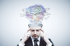 Creative mind concept. Pensive businessman with abstract brain sketch on light background. Creative mind concept royalty free stock photo