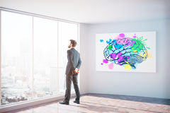 Creative mind concept. Side view of businessman looking out of window in interior with city view daylight and colorful brain sketch on poster. Creative mind royalty free stock photography