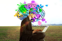 Creative mind concept. Side view of young businessman with colorful brain sketch using laptop in the middle of field. Creative mind concept royalty free stock image
