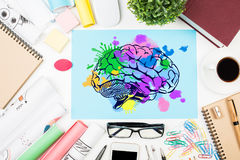 Creative mind concept. Top view of messy office desktop with coffee cup, supplies and colorful brain sketch. Creative mind concept royalty free stock photography