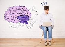 Creative mind concept. Young businessman sitting on chair and using laptop in bright interior with brain sketch on wall. Creative mind concept royalty free stock images