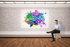 Creative mind concept. Young businessman using laptop in interior with colorful brain sketch. Creative mind concept. 3D Rendering stock photos