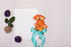 Creative mock up with a card and orang rose. Empty sheet of paper. Royalty Free Stock Images