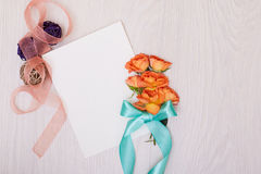 Creative mock up with a card and orang rose. Empty sheet of paper. Stock Photo