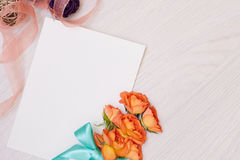 Creative mock up with a card and orang rose. Empty sheet of paper. Royalty Free Stock Photos