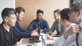 Creative multiethnic business team in the modern conference room discuss work results. Siiting at the table against big window background. Focus on handsome stock video footage