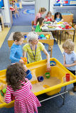 Creative Nursery Lesson. Elevated view of teachers doing activities with children in nursery. Some are playing in a sand box and the others are making crafts stock photography