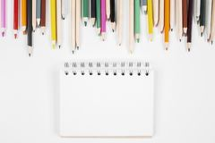 Creative office desktop. Top view of white office desktop with colorful pencils and notepad. Mock up Stock Photography