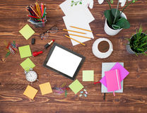 Creative office supplies and tablet on wooden background Royalty Free Stock Photo