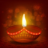Creative Oil Lamp for Happy Diwali celebration. Glossy realistic illuminated Oil Lamp (Diya) on beautiful rangoli, Creative glowing festive background, Elegant Royalty Free Stock Image