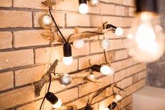 Creative original Christmas decoration. Bulbs at the brick wall background. Stock Photo