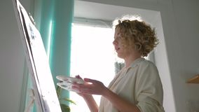 Creative painter female with muse paints picture with bright colors on white canvas on easel at art studio against. Sunlit window, shooting in motion stock video