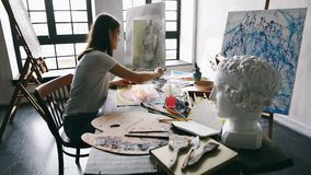 Creative painting work space. Artist Girl is working. Creative workshop filled with sculpture and artwork. Big windows. Natural daylight. Inspiration mood stock footage