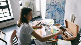 Creative painting work space. Young Artist Girl is working. Creative workshop filled with sculpture and artwork. Big. Windows natural daylight. Inspiration stock footage