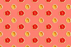 Creative pattern of slices of grapefruit and lemon on coral background. stock photo