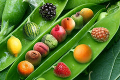 Creative pea with different fruits instead grains of pea. Creative pea with different fruits and vegetables instead grains of pea royalty free stock photography