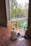 Creative pensive artist painting in colorful Spanish square in Seville, Spain Stock Image
