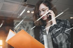 Creative pensive manager woman in glasses talking on smartphone stock image