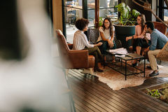 Creative people doing a brainstorming meeting in a modern office. Corporate professionals meeting in office lobby. Creative people doing a brainstorming meeting royalty free stock images