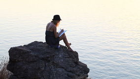 Creative personality with a notebook on the riverside during sunset stock footage