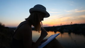 Creative personality with a notebook on the riverside during sunset stock video