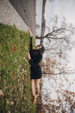 Creative photo of a brunette girl in autumn Park. Woman hanging from edge, lying on the green grass. Look at the world from side Stock Images