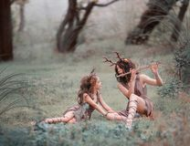 Creative photo idea for mom and daughter, child and mother dressed as deer are sitting on the grass in the forest, a stock photo