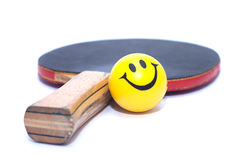Rackets of table tennis with yellow fun emoticon ball. Creative photo of tennis table racket with yellow emoticon ball Royalty Free Stock Photos